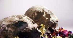 Cranio e varie caramelle contro fondo bianco 4k stock footage