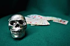 Cranio, piattaforma delle carte su una tavola verde Tavola del casinò fotografia stock libera da diritti
