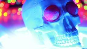 Cranio su fondo variopinto defocused, testa spaventosa di Halloween video d archivio