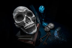 Cranio sui libri e sulle sfere di cristallo di magia con le chiavi arrugginite Fotografie Stock Libere da Diritti