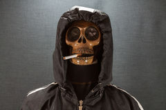 Cranio umano che fuma una sigaretta su un fondo nero, sigaretta molto pericolosa per la gente Non fumi prego Giorno di Halloween immagine stock libera da diritti