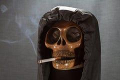 Cranio umano che fuma una sigaretta su un fondo nero, sigaretta molto pericolosa per la gente Non fumi prego Giorno di Halloween Immagini Stock Libere da Diritti