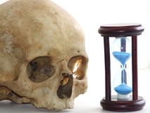 Cranio umano con l'orologio blu della sabbia Fotografia Stock