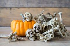 Cranio umano su fondo, sullo scheletro e sulla zucca di legno su legno, fondo felice di Halloween Immagini Stock