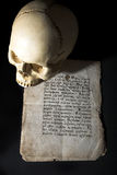 Cranium and old manuscript. Isolated on black background stock image
