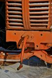 Crank of an old tractor. The grill plate and crank of an old orange tractor is partially covered by the winter snow Stock Photo