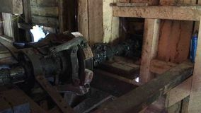 The crank shaft of an old water-wheel. A mechanism powered by water turning inside the historic mabry grist mill in virginia stock footage