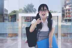 Cranky asian female student in front of university. While shouting and pointing at the camera Royalty Free Stock Photo