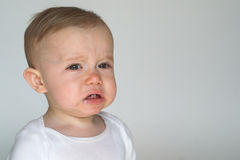 Cranky Baby. Image of cute whining baby sitting in front of a white background Stock Image