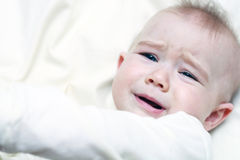 Cranky baby. Portrait of cranky baby on a light background Royalty Free Stock Photo