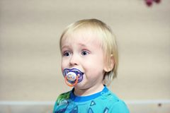 Cranky baby cries. Cranky unhappy baby is sitting and crying out loud royalty free stock images