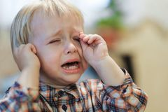 Cranky baby cries. Cranky unhappy baby is sitting and crying out loud royalty free stock photo