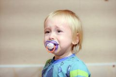 Cranky baby cries. Cranky unhappy baby is sitting and crying out loud royalty free stock photos