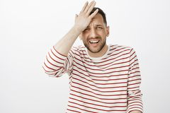 Crap I forgot about meeting. Portrait of embarrassed handsome troubled guy in striped pullover, punching forehead and. Grimacing, remembering something Stock Photography
