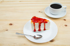 Crape cake with strawberry sauce and cup of coffee. On wooden table Royalty Free Stock Images