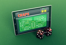 Craps online. Top view of a tablet pc with a craps app and a couple of dice on green background (3d render Royalty Free Stock Photo