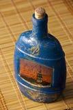 Craquelure decoupage bottle on a mat Stock Images