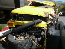 Crash. A wrecked yellow SUV strapped to a trailer Royalty Free Stock Images