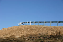 Crash barrier. A roadside crash barrier against a blue sky Royalty Free Stock Photo