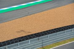 Crash barrier with pebbles, Asphalt road circuit and safety fence on race track. Race Track Construction kit. Crash barrier with pebbles, Asphalt road circuit stock photography