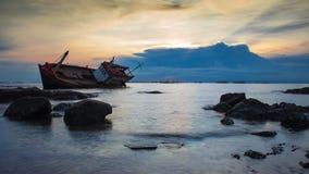 Crash boat on sea during sunset Stock Photo