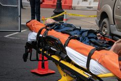 A crash dummy mannequin displayed on a stretcher on the street stock image