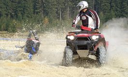 Crash at the sand pit. ATV racer falling into a pit filled with water Stock Image