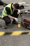 Crash site investigation. Policeman is numbering evidences in car accident Stock Image
