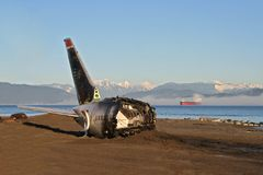 Crash site tail section. Commercial aircraft crash site on beach with fog sea and mountains in background (props for film set Stock Image
