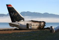 Crash site tail section2. Wreckage of commercial airliner on beach with fog and mountains in distance (film set Royalty Free Stock Image
