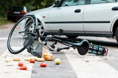 Crashed bike after traffic accident. Crashed bike lying on the street near a car after traffic accident Stock Photos
