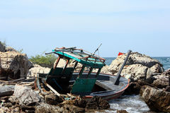 Crashed boat in rocks Royalty Free Stock Photos
