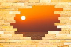 Crashed Brick Wall with sun set over the sea behind Stock Images