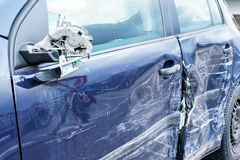Crashed car, detail on side mirror and door - metal plates deformed after accident hit.  stock image