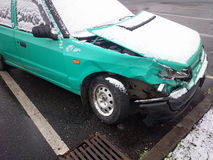 Crashed car. Green wreck under dusting of snow Royalty Free Stock Images