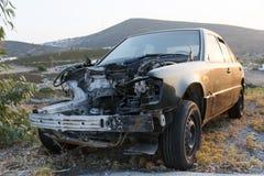 A crashed car in a junk yard. A crashed black car in a junk yard Stock Image
