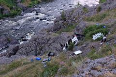 Crashed Car Near A Mountain River With Rapids, Debris Scattered All Over The Rocky Shore On The Bank Of Trees Stock Photos