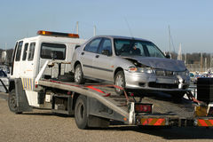 Crashed Car on Trailer. Damaged Car on Trailer Lorry Royalty Free Stock Photo