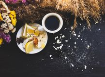Crashed macaroons in a white plate. Coffee time. Crashed macaroons on a white plate with coffee and some dry flowers royalty free stock images