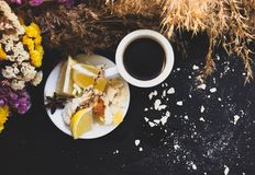 Crashed macaroons in a white plate. Coffee time. Crashed macaroons on a white plate with coffee and some dry flowers royalty free stock photo