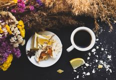 Crashed macaroons in a white plate. Coffee time. Crashed macaroons on a white plate with coffee and some dry flowers stock photography