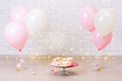 Crashed party background - smashed cake over brick wall with lights and balloons. Crashed party background - smashed cake over brick wall with lights and royalty free stock photo