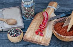 Red hot chili pepper and peppercorn and recipe book on dark wooden background. Crashed Red hot chili pepper and peppercorn and recipe book on dark wooden Royalty Free Stock Photo