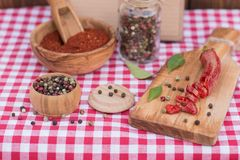 Red hot chili pepper and peppercorn and recipe book on picnic cloth. Crashed Red hot chili pepper and peppercorn and recipe book on picnic cloth Royalty Free Stock Images