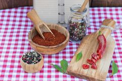Red hot chili pepper and peppercorn and recipe book on picnic cloth. Crashed Red hot chili pepper and peppercorn and recipe book on picnic cloth Stock Photos