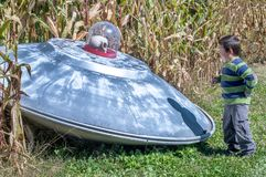 Crashed UFO and little boy royalty free stock images