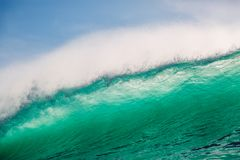 Crashing big green wave. Breaking barrel wave with sun light Royalty Free Stock Photos