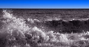 Crashing black and white waves with blue sky. Black and white scene with crashing waves and blue sky background Royalty Free Stock Photography