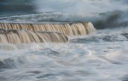 Crashing sea waves and small waterfalls Royalty Free Stock Photo