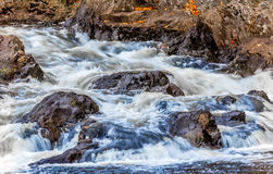 Crashing Water in Stream. Water crashing over rocks in stream with autumn color leaves on shore Stock Photos